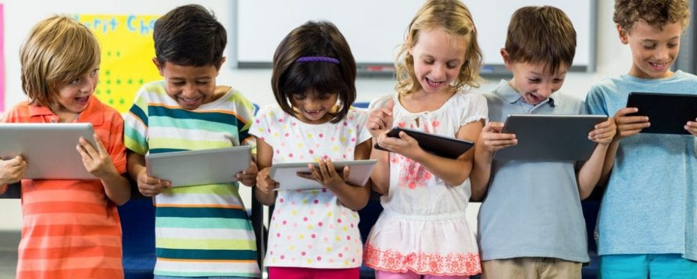 Smiling schoolchildren using digital tablet
